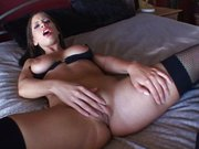 Lustfully masturbating girl on big bed