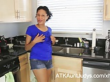 Carmen toys her pussy a little in the kitchen.